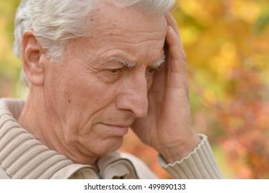 Sad elderly man in autumn park