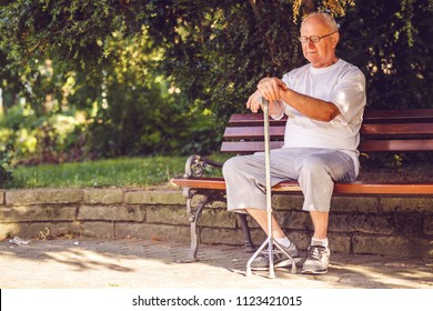 Sad elderly man with his walking stick sitting on bench in the park