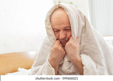 Sad elderly man suffers from insomnia. He covered himself with a blanket to make it easier to fall asleep and it was not cold.