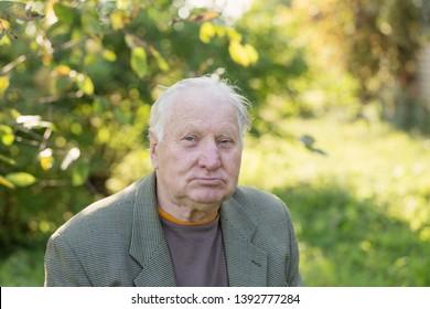 sad elderly man in sunny park
