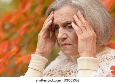 Sad elderly woman in autumn park