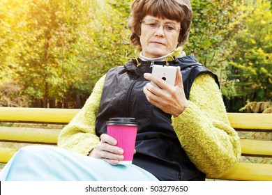 Sad elderly woman with cup of coffee checking e-mail, using wireless Internet connection on smart phone while sitting alone in public park. Old woman sitting in the park with cellphone.