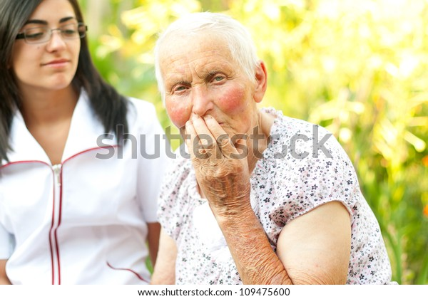 Sad elderly woman with her hand on her mouth.