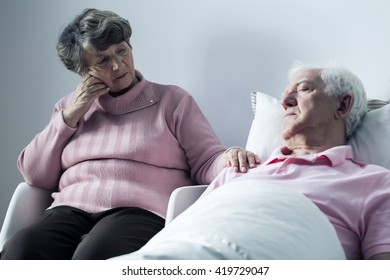 Sad elderly woman and her sick husband lying in a hospital bed