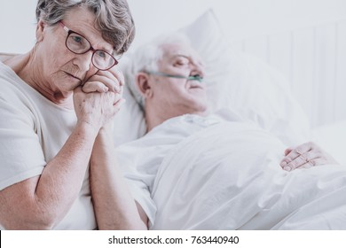 Sad elderly woman taking care of her dying husband with alzheimer's
