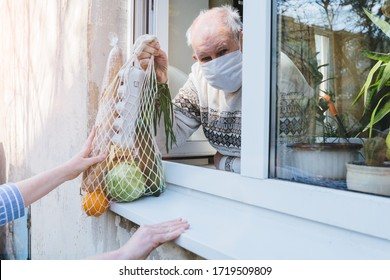 A sad elderly wrinkled woman is looking through the window in the protective mask of her house. Self-isolation of the elderly coronavirus covid-19. Quarantine and isolation to keep old people healthy