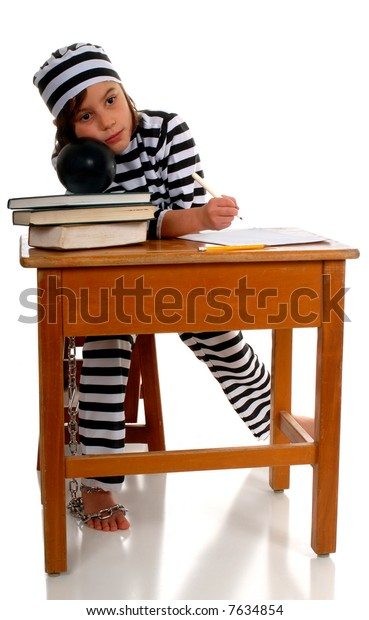 A sad elementary girl sitting at a school desk in a striped prison uniform, a ball and chain attached to one leg.