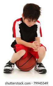 Sad elementary school boy sitting on basketball sad crying expression on face.