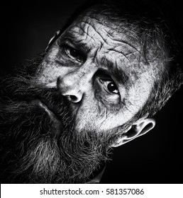Sad emotional portrait image of an old man. Senior dark black and white portrait closeup of man face looking worried and anxious. Face and eyes looking into camera, wrinkled skin.
