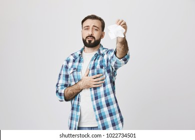 Sad european father expressing sorrow because of departure of close friend, holding one hand on heart and waving tissue with another, over gray background. Man feels heartbroken and says goodbye