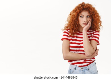 Sad european redhead curly woman lean head palm boredom regret look left jealous sitting boring office dream party standing upset unhappy striped t-shirt reluctant white background