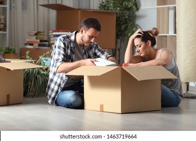 Sad evicted couple moving home boxing belongings sitting on the floor in the night