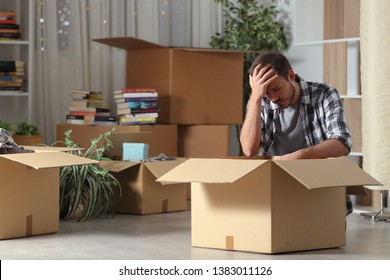 Sad evicted man moving home complaining sitting on the floor in the night