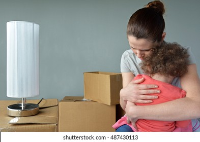 Sad evicted mother (age 30-35) with child (age 2-3) worried relocating house.  Moving house concept. Real people. copy space