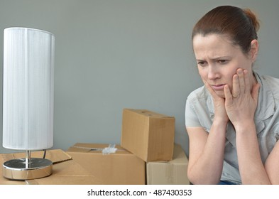 Sad evicted woman (age 30-35) worried relocating house.  Moving house concept. Real people. copy space