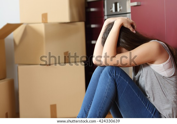 Грустная выселяющая женщина переживала переезд дом, сидя на полу в кухне