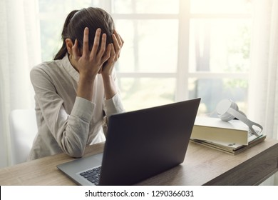 Sad exhausted woman working with her laptop at home, she is holding head in hands