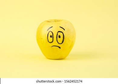 sad Face on an apple - abstract image of human emotions on a yellow background