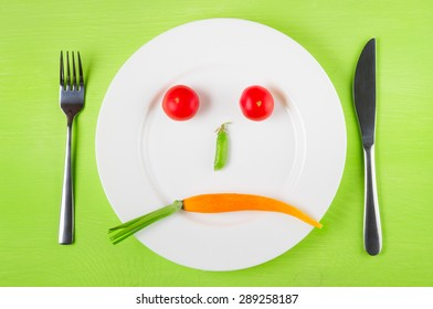 Sad face of vegetables, the concept of dietary restrictions, healthy lifestyle, diet,  weight loss, anti-obesity, healthy diet. Two tomatoes, peas in a pod and carrots on a plate, knife, fork