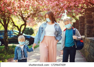 Sad family going home during quarantine. Family wearing face masks. Springtime. Health care concept. Back to school. Education. Real life 2020. Mother and pupil of primary school go hand in hand.