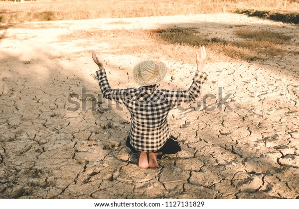 Sad farmer on the cracked dry ground due to drought, natural disaster. Affected of global warming made climate change. Water shortage - drought and crisis environment concept.