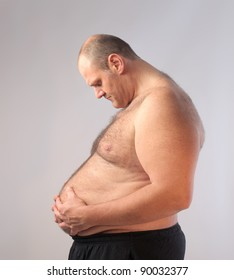 Sad fat bare-chested man looking at his tummy
