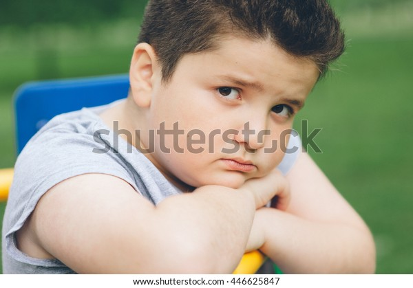 smutný tlustý chlapec sedí na sportovním simulátoru