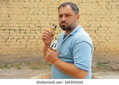 Sad fat male smeared with ice cream