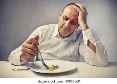 Sad fat man eating vegetables