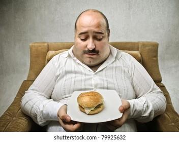 Sad fat man looking at a hamburger on his dish