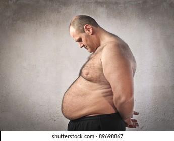 Sad fat man looking at his tummy