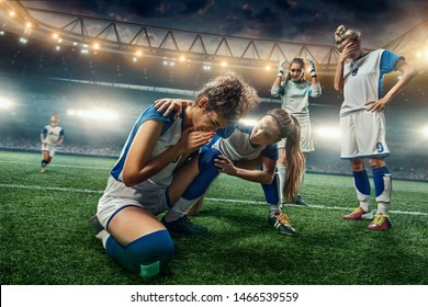 Sad Female Soccer players on a professional soccer stadium. Girls Team crying