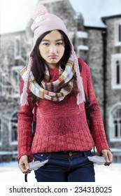 Sad female student having financial problem and showing empty pockets near the school building