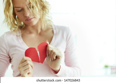 Sad female tearing up red broken paper heart