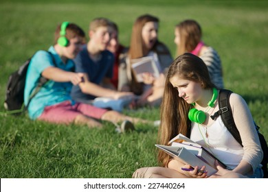 Sad female teenager sitting outdoors with books