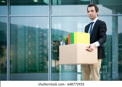 Sad fired businessman taking away his belongings from the financial district