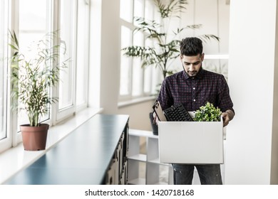 Sad fired indian male office worker holding box of his personal stuff
