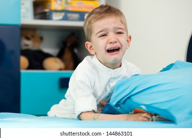 A sad five year old child sitting next to his bed with holding a pillow and crying
