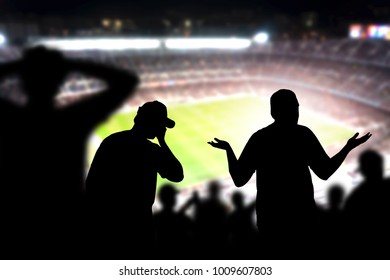 Sad football fans. Disappointed, angry and upset crowd in a match in a soccer stadium. Favourite team and club lost game. Devastated audience in live sport event. Angry silhouette people watching.