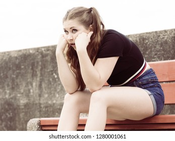 Sad funny teenage woman being worried. Frustrated female waiting for somebody while sitting on bench outdoor.