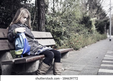 Sad girl after school, sitting on bench