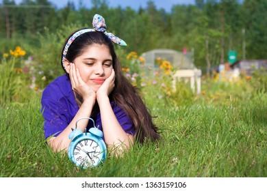 Sad girl with alarm clock in summer garden