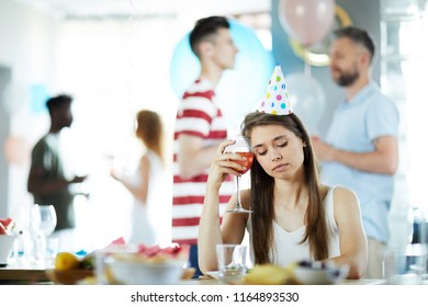 Sad girl in birthday cap sitting by table with drink by her temple on background of talking friends