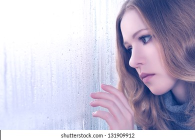 sad girl is bored and sadness at the window in the rain