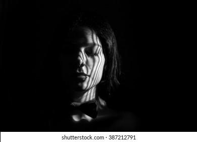 sad girl with closed eyes in dark, monochrome