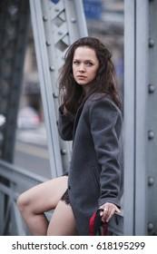 sad girl in a coat sitting on the iron bridge
