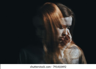Sad girl crying because of anxiety and personality disorder. Black background with copy space
