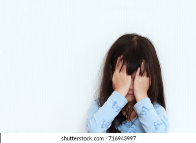 Sad girl crying,girl sat with her hands closed on her face.The girl hide the tears ,sitting at the corner of the room.