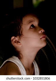 Sad girl in the darknesses,Little Asian girl  look worried and stress under the candlelight. Girl may be in trouble or unhappy.She looking up into sky looking for something or she may prays to god.