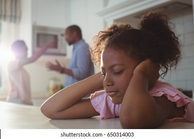 Sad girl fed up of her parents arguing in kitchen at home